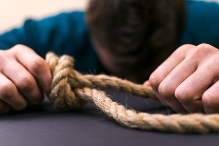 A man holds a loop of rope in his hands. A mental health day. Stock Photo