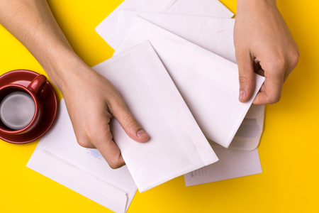 A man sorts the mail. Male hands the envelopes on a yellow background, a red coffee Cup.
