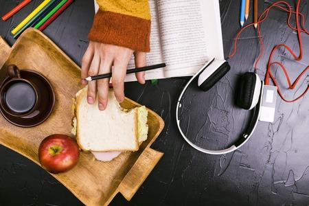 A man reads, translates the text. Sandwich, headphones, pencils, notebooks Still life black background