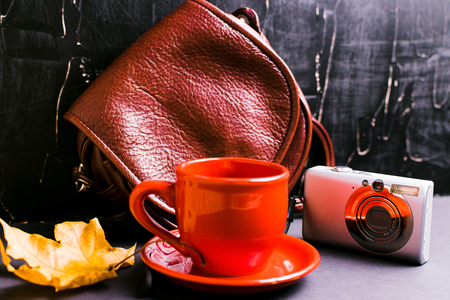 Womens accessories, gloves, scarf, coffee, and other objects on a dark textured background. Stock Photo