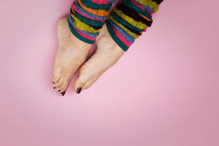 Female feet in socks on a pink background 免版税图像 - 90600869