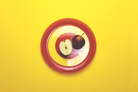 Apple on a red plate on a colored background Stock Photo