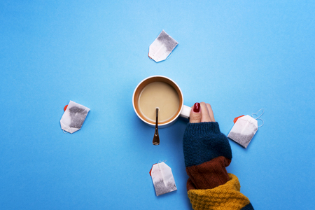 Girl holding a Cup of coffee surrounded by tea bags. The concept of beverages and preferences. Coffee pause, a break.