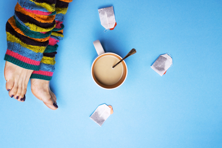 Girl in socks and surrounded by coffee and tea. The concept of stopping for coffee breaks. Drinks. Stock Photo