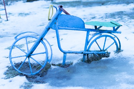 The old childrens bike froze in the snow. Playground