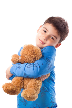 Cute boy in pajamas hugging a teddy bear photo