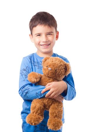 waist deep: Cute boy in pajamas hugging a teddy bear