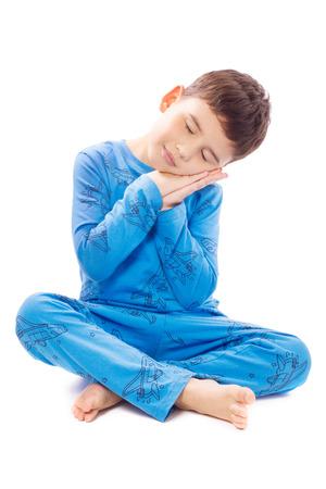 Jongen in pyjama zit met gevouwen handen onder zijn wang Stockfoto