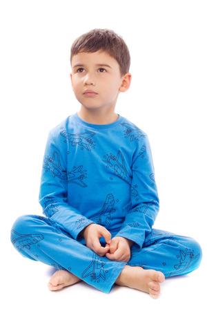 Schattige jongen zit in kleermakerszit op een witte achtergrond Stockfoto