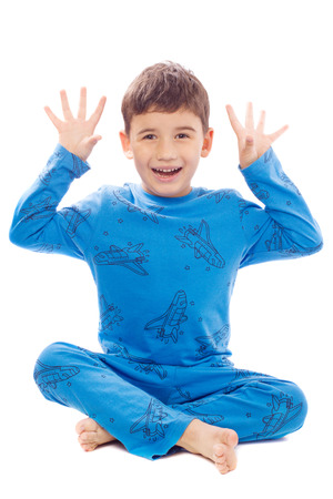 legs around: Portrait of cute naughty boy in pajamas with terrifying hands up