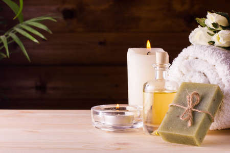 Image of spa concept with flowers, candles, sea salt, oil, towel and natural bar of soap photo