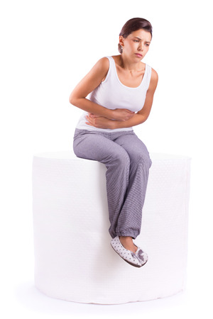 Portrait of woman with stomach ache sitting on a roll of toilet paper, her hands on abdomen photo