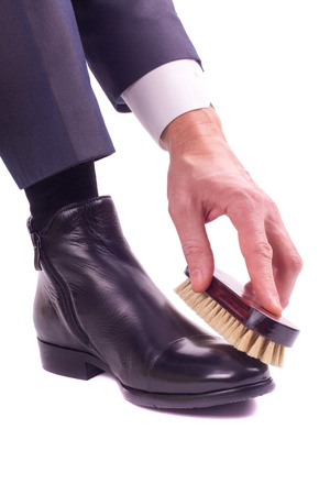 A businessman cleans leather shoes with brush shoe in his hand photo