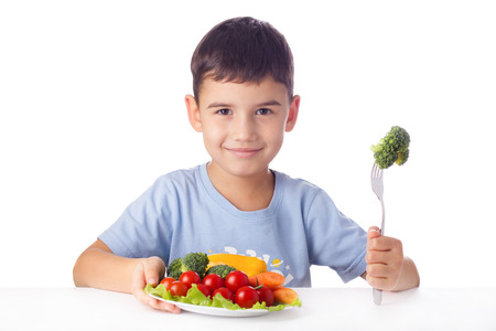 Happy child eating healthy vegetables photo
