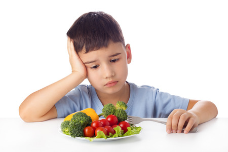 Sad boy doesn't want eat healthy vegetables Standard-Bild