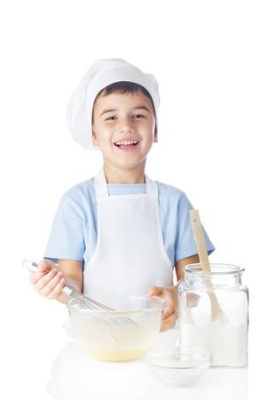 Cute boy mixes ingredients for sponge cake photo