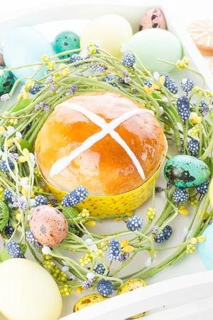 Hot cross buns and easter decorations. Wicker nest, painted eggs, homemade gingerbread cookies