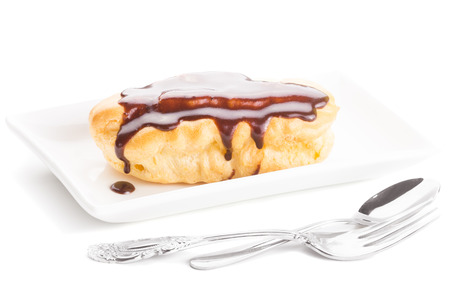creampuff: Chocolate eclair on a white plate with an elegant fork, isolated on white Stock Photo