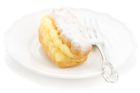 creampuff: Eclair with powdered sugar filled custard on a white plate with an elegant fork Stock Photo