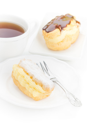 Chocolate eclair dessert powdered sugar filled custard on a white plate with an elegant fork and cup of tea photo