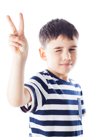 Portrait of smiling boy, he shows hand victory sign photo