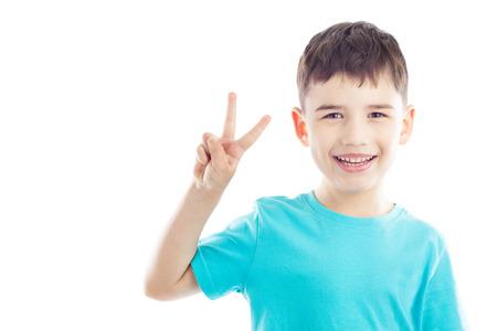 simbolo della pace: Ritratto di ragazzo sorridente, mostra la vittoria mano segno