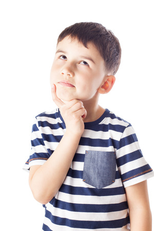 The boy lost in thought, looking up, his finger in chin Stock Photo
