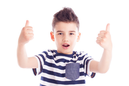 Portrait of a cute boy giving thumbs up gesture with satisfied expression photo