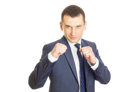 Young businessman in an aggressive fight pose wearing an elegant suit
