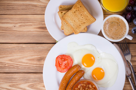 Traditional English breakfast with sausage, fried eggs, beans, coffee and orange juice photo