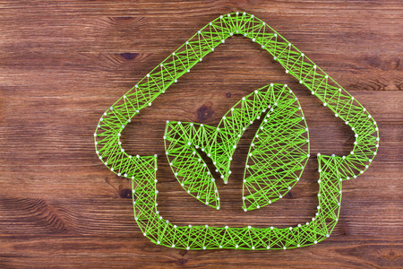 Concept of green eco-friendly house on wooden background. Handmade string art. photo
