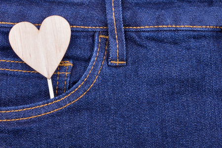 declaration: Denim texture background and pocket with wooden heart shape, declaration of love concept.