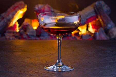 A glass of classic Manhattan cocktail on fireplace background