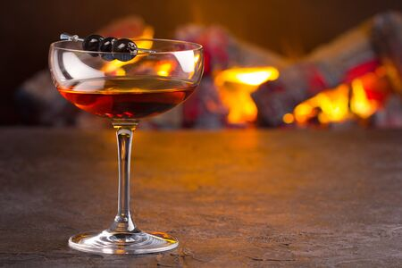A glass of classic Manhattan cocktail on fireplace background 版權商用圖片 - 132642887