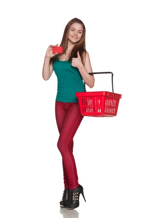Happy shopping female holding blank credit card and shoping red cart, isolated on white background photo