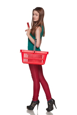 Happy shopping female holding blank credit card and red cart over white background photo