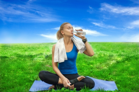 Portrait of a young woman refreshing during yoga workout at the carpet  Outdoor photo