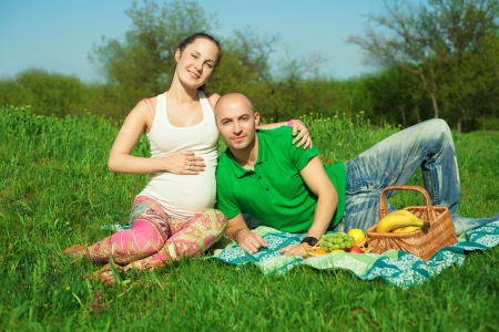 young happy pregnant woman with young man lying on the grass having picnic photo