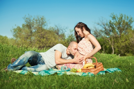 Married pregnant couple at the park having picnic. Husband kissing wifes belly photo