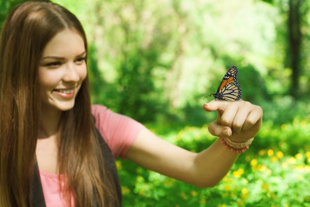 big girl:  butterfly sitting on the finger of a young woman in the park, focus at the butterfly