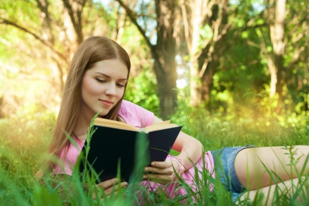 Girl reading book, while lying in the grass at park photo