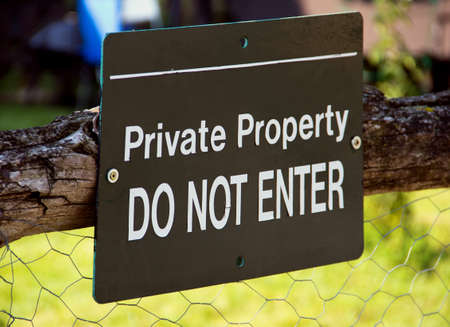 Private Property sign at the countryside hanging on the old wooden fence