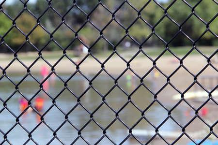 trespassing: Beach with people at the iron net fence  Stock Photo