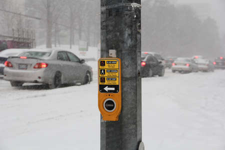 Pedestrian traffic stop button close up with snow storm on the background photo
