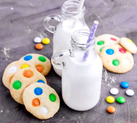 Milk and homemade cookie with colored chocolate candy