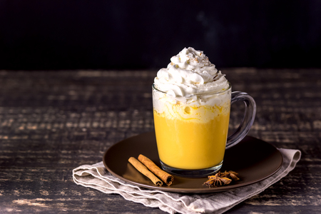 Tasty Pumpkin Latte with Spices Whipped cream on top on a Dark Wooden Background Autumn Hot Beverage