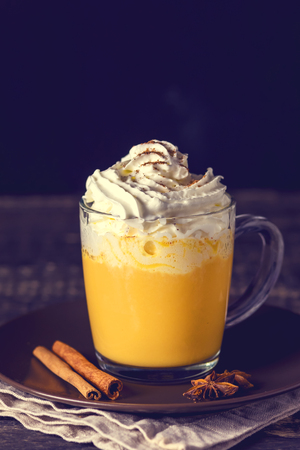 Tasty Pumpkin Latte with Spices Whipped cream on top on a Dark Wooden Background Autumn Hot Beverage Toned