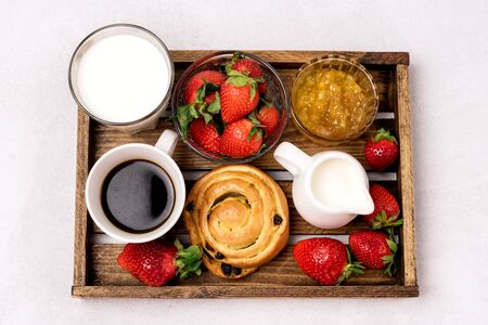 Wooden Tray with Breakfast Freshly Baked Buns with Raisins and Cinnamon Cup of Black Coffee Cream Ripe Strawberry and Orange Jam in Glass Bowl