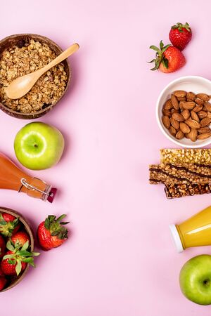 Breakfast Concept Healthy Diet Food Coconut Bowl with Muesli Bowl with Ripe Strawberry Green Apple Muesli Bars Bottles of Citrus Juice Pink Background Horizontal Copy Space 免版税图像