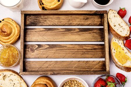 Tasty Breakfast Freshly Baked Buns with Raisins and Cinnamon Fresh Homemade Bread Cup of Black Coffee Cream Ripe Strawberry and Orange Jam in Glass Bowl Top View Copy Space Frame Muesli